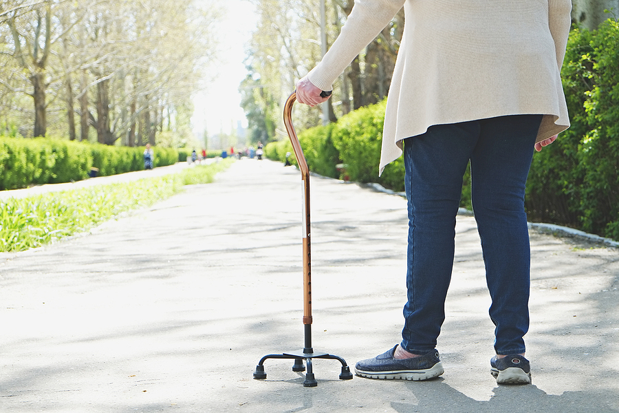 Senior disabled caucasian woman hands on cane outside nursing home park. Close up of elderly lady holding a walking stick outdoors of healthcare facility on the sunny day.