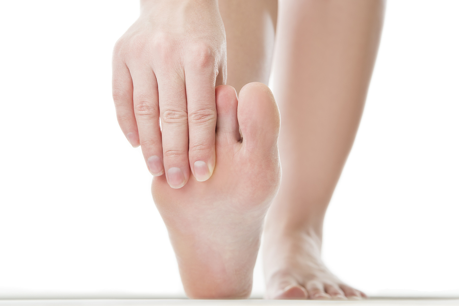 Massage of female feet. Pedicures.Pain in the foot. Isolated on white background.