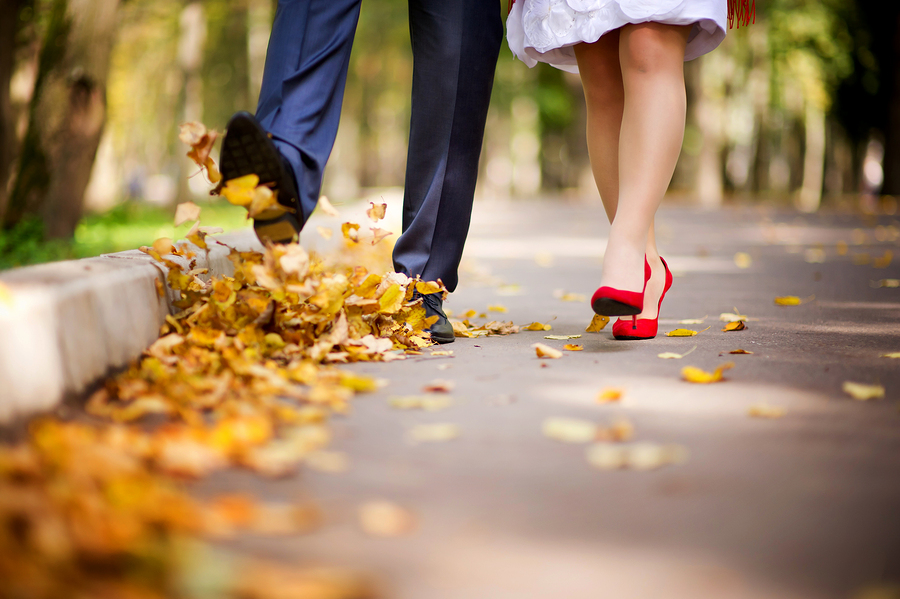 the couple walks through the park in the autumn and throws their fallen leaves into the air with their feet. Kicking the leaves. Close-up, no faces
