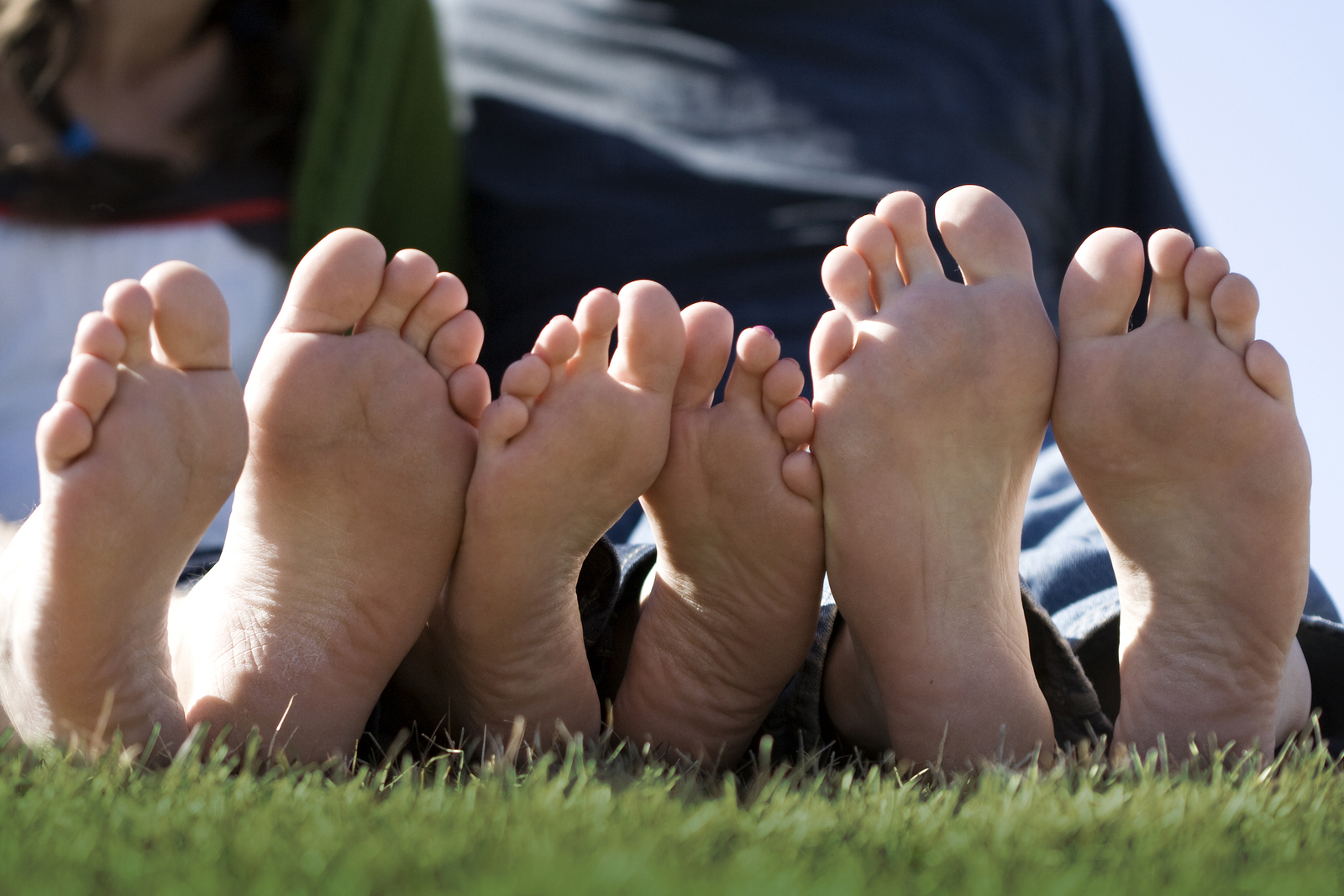 Three sets of clean happy feet all in a row on a sunny day. This is a great photo for a foot doctor (Podiatry or podiatric medicine) website or marketing materials. ** Note: Slight blurriness, best at smaller sizes