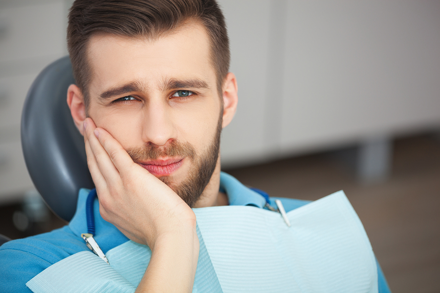 Shot of a young man with tooth pain while sitting in a dentist's chair.