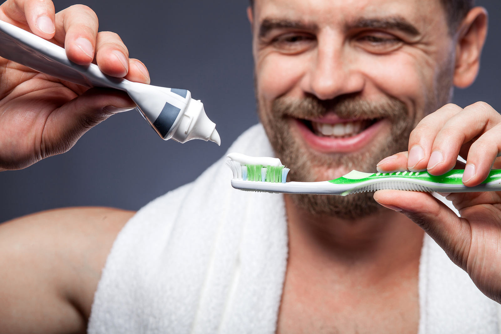 Close up of attractive young bearded man is brushing his teeth. He is standing and smiling. The man is squeezing tooth-paste into tooth-brush. Focus on cleaning tools
