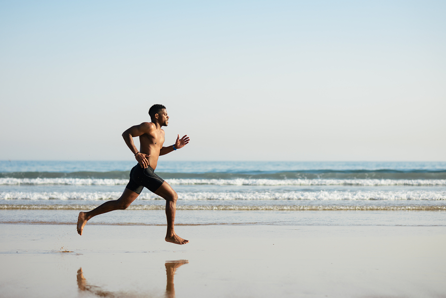 Black fit man running barefoot by the sea on the beach. Powerful runner training outdoor on summer.