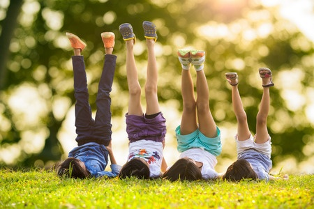 26772943 - group of happy children lying on green grass outdoors in spring park