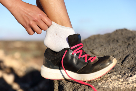 55645917 - runner putting on fitness shoes and running shoes closeup outdoors on mountain background. female athlete getting ready for marathon race preparing her feet on trail run.