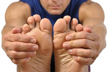 14302602 - closeup of bottom of bare feet of male athlete as he holds feet to do hamstring stretch on white background