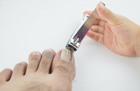 37505112 - nail clipper cutting man toenails by little hand