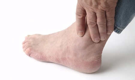 13973734 - a man tends to his sore ankle