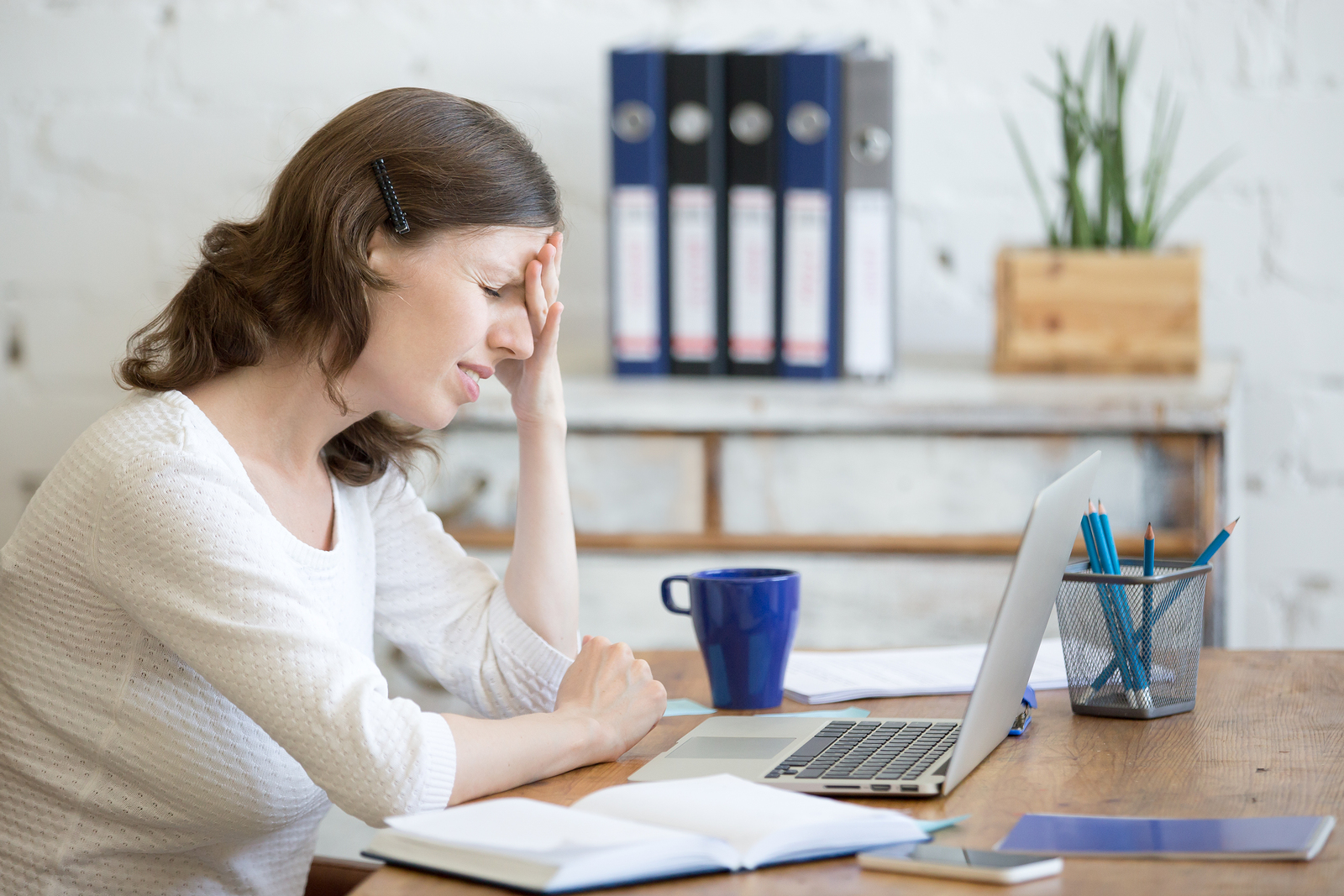 Young stressed businesswoman sitting in front of laptop and touching head with pained expression. Business person feeling pain suffering from migraine after working on pc overworked or depressed